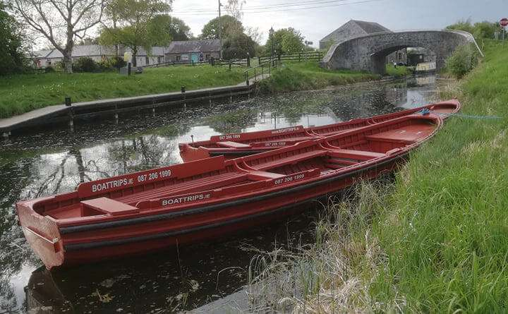 Two red Traditional Open-Boats moored on the Grand canal at Vicarstown. Stone bridge in the background