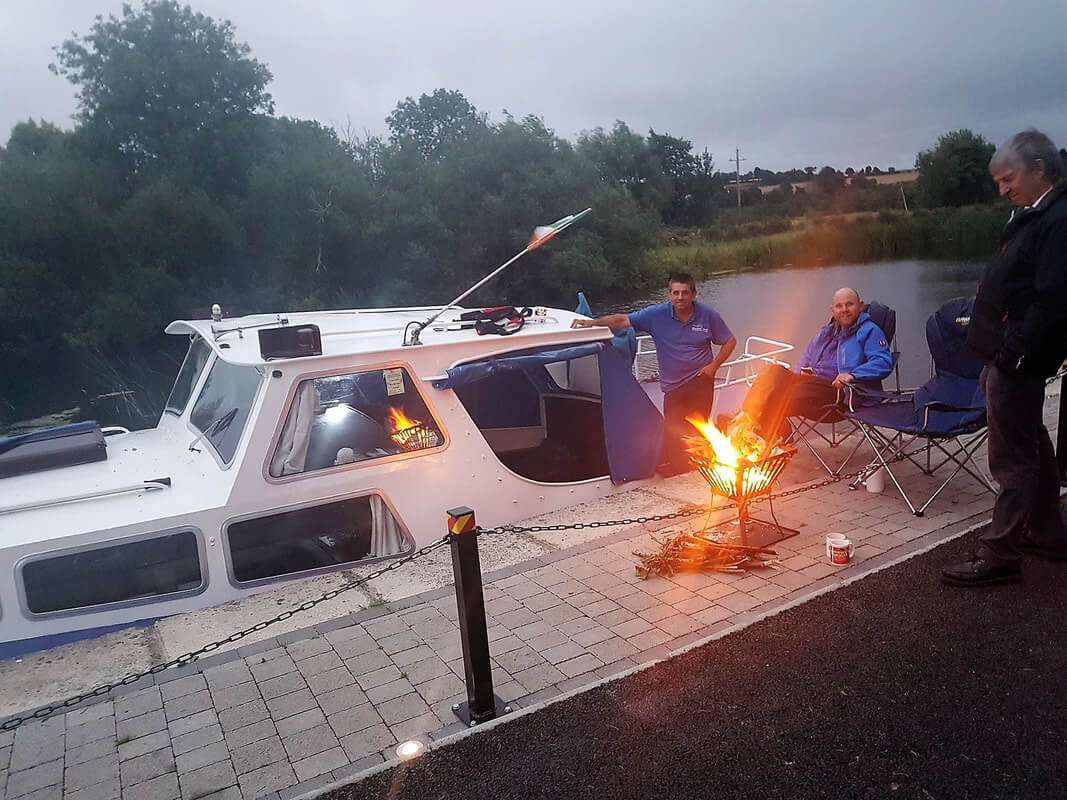 Campfire beside moored boats on river Barrow