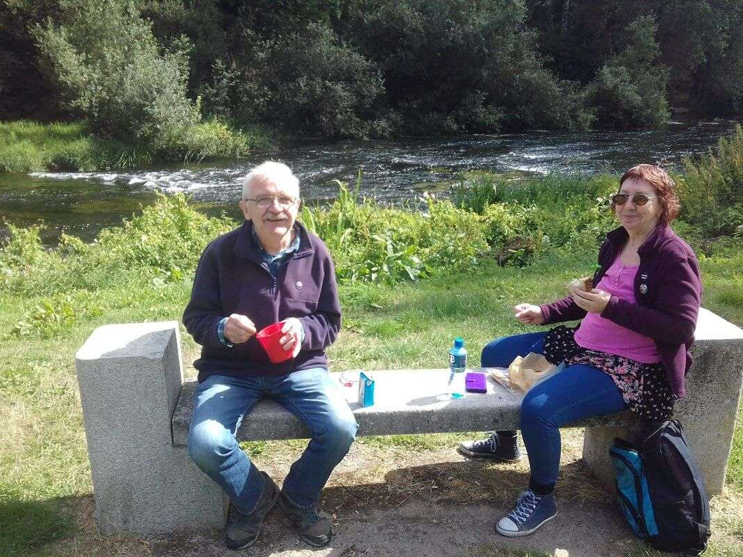 Two people having a picnic on a stone bench
