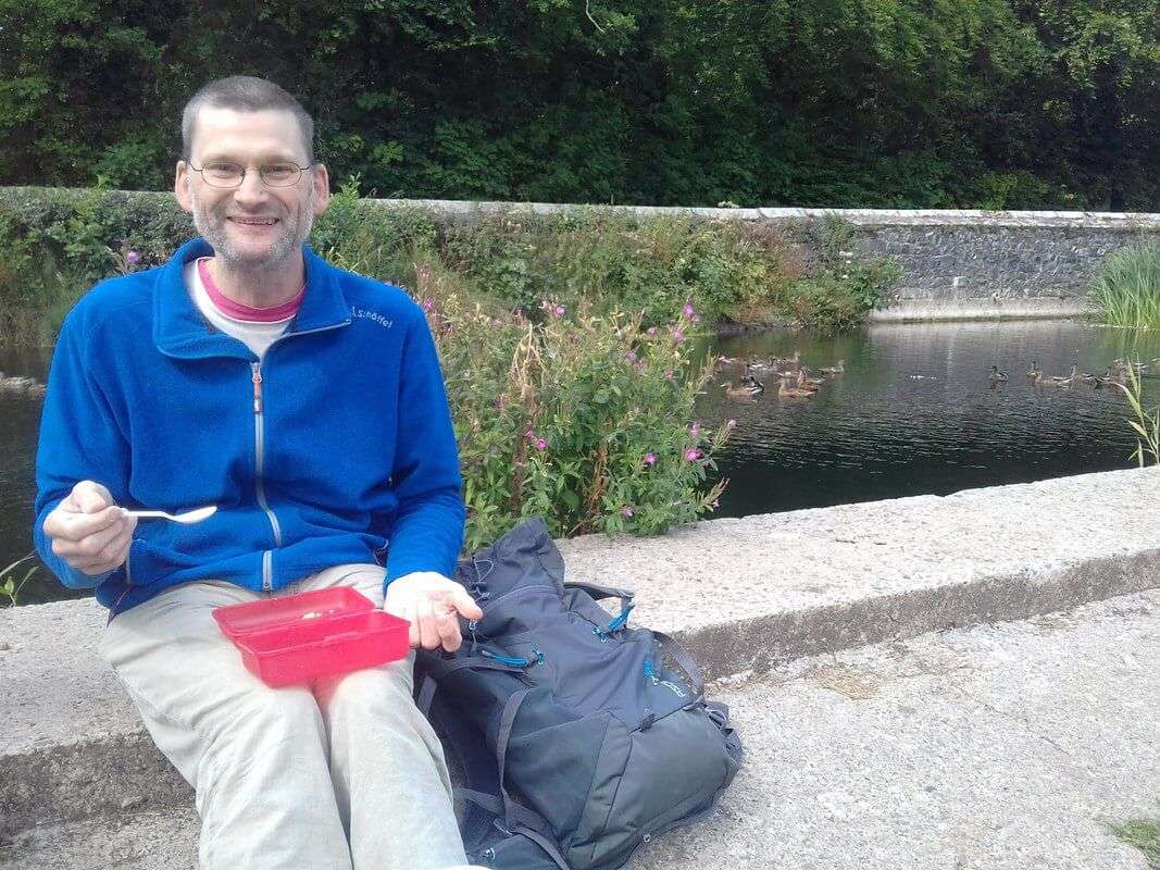 A man eating lunch by the river