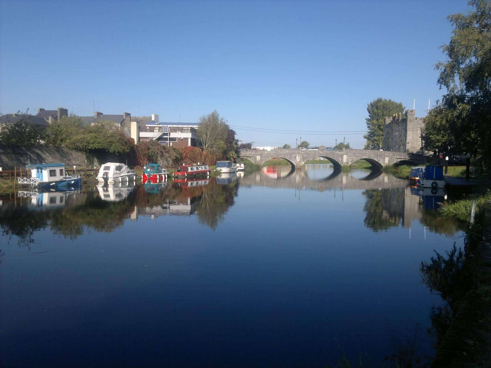Picture of Athy Town taken from the water. In the middle background is a stone bridge called Crom-a-boo and next to it is Whites Castle. On either side of the river , boats are moored. The sky in bright blue and reflected in the river.