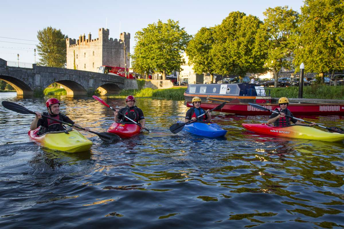 Colourful kayakers on a river with boat and castle behind.