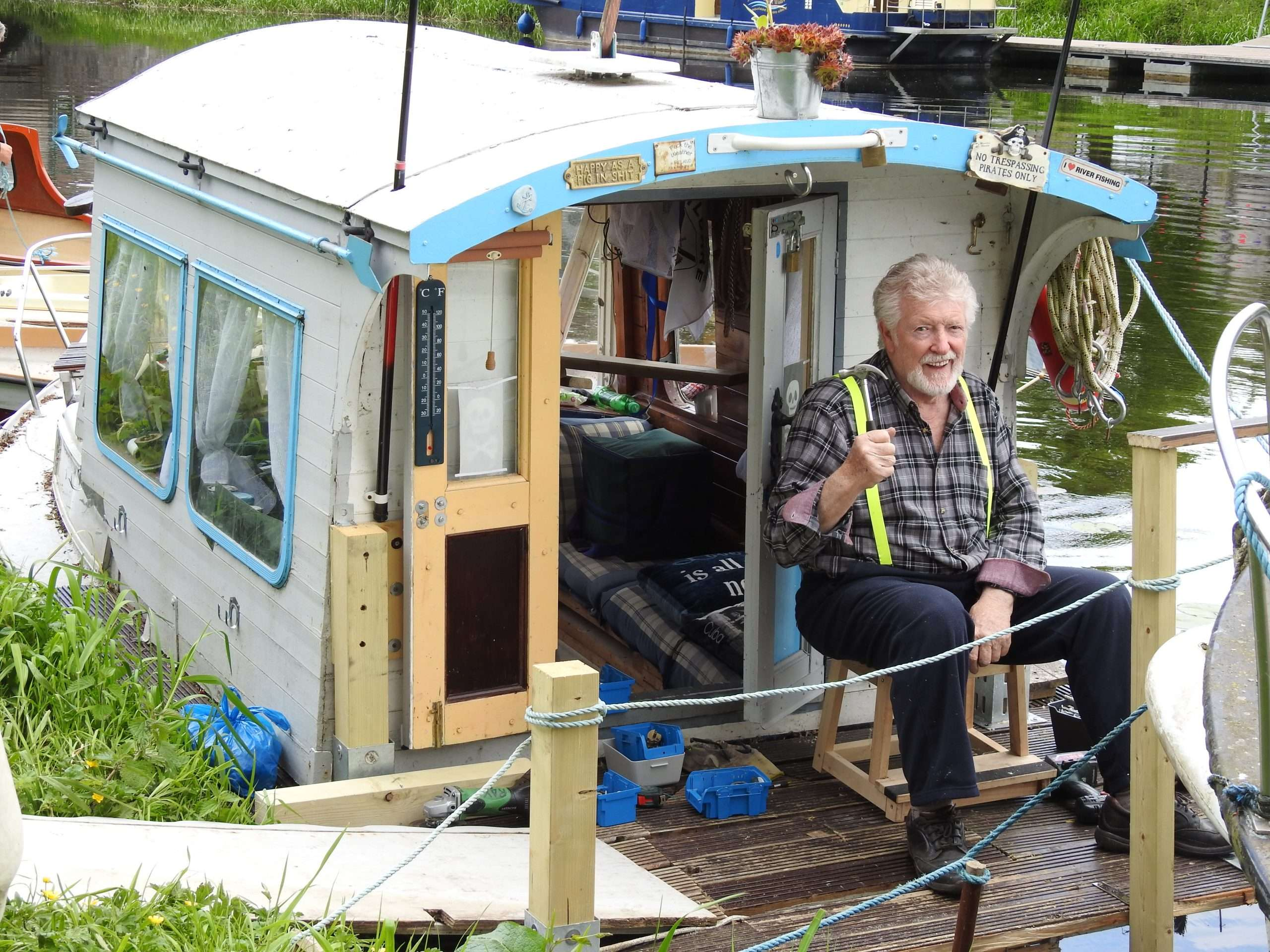 Retired Ray Byrne sitting at cabin door of boat