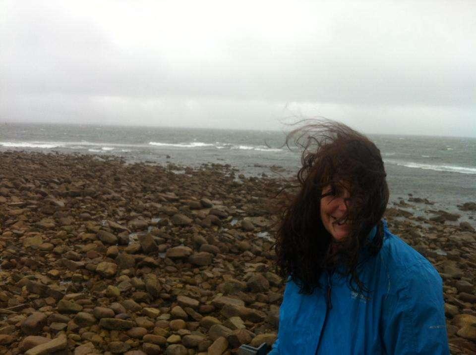 Ann Marie Dunne on a rocky coastline in windy weather. Hair blowing in the wind.