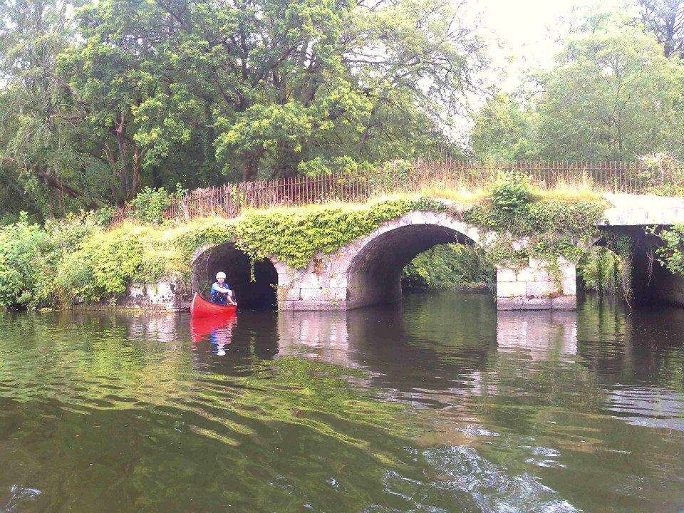 Canoer under bridge at mouth of Mountain River