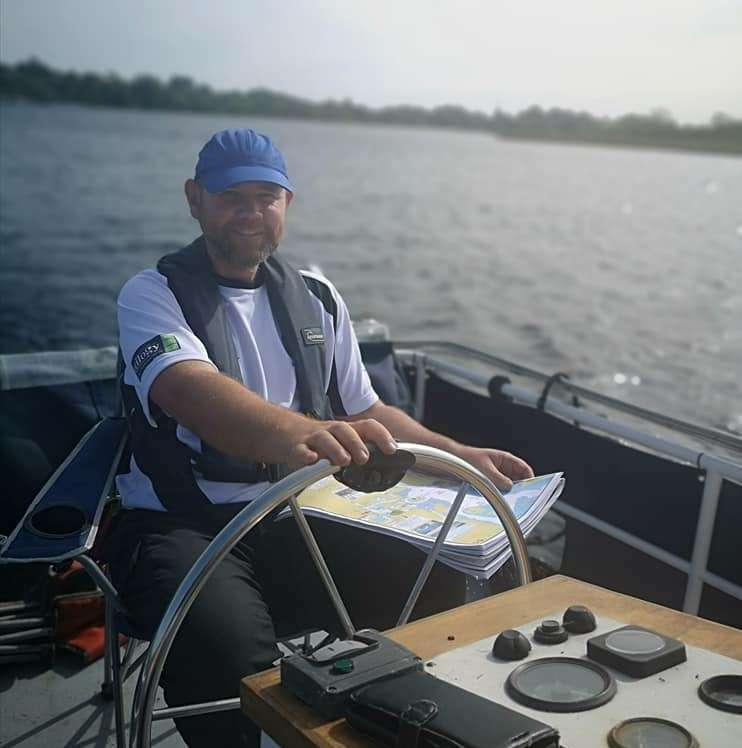 Cliff Reid at the helm of a cruiser on river Shannon
