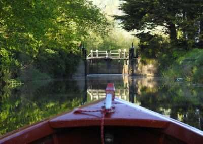 Bow of boat entering Clogrennan Lock on river Barrow Navigation during summer. Breast lock gates open.