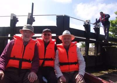 Three men wear orange lifejackets on a boat in a lock. Lock Keeper working the lock gates.