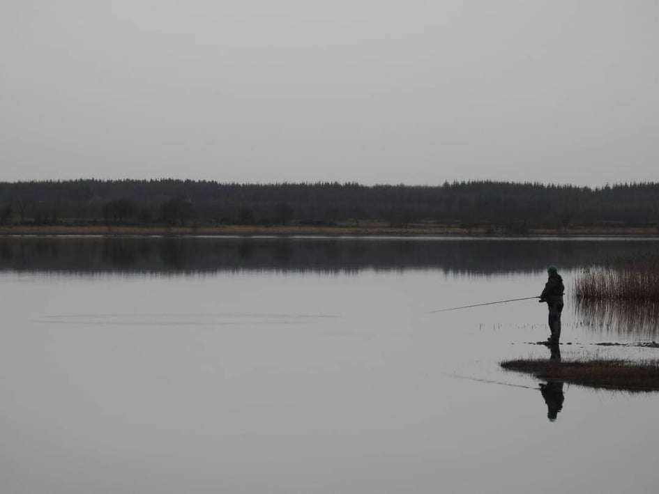 Fisherman on side of Lough O'Flynn lake in grey overcast day