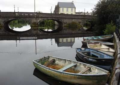 Small boats moored on river Barrow at Graiguecullen, Carlow, Ireland. Bridge in background.