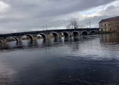 Bridge and malt stores on river Barrow in Goresbridge, Ireland on a grey day.