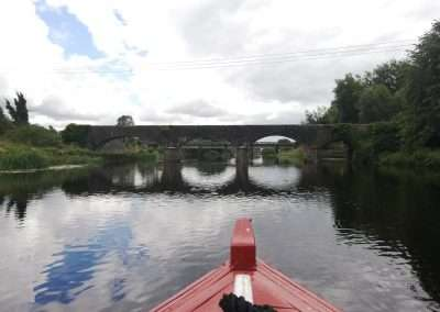 Bow of red boat approaching the Horse Bridge on river Barrow at Athy, Kildare, Ireland.