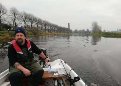 John Creaney driving a small boat on river Barrow at Athy, Kildare, Ireland.