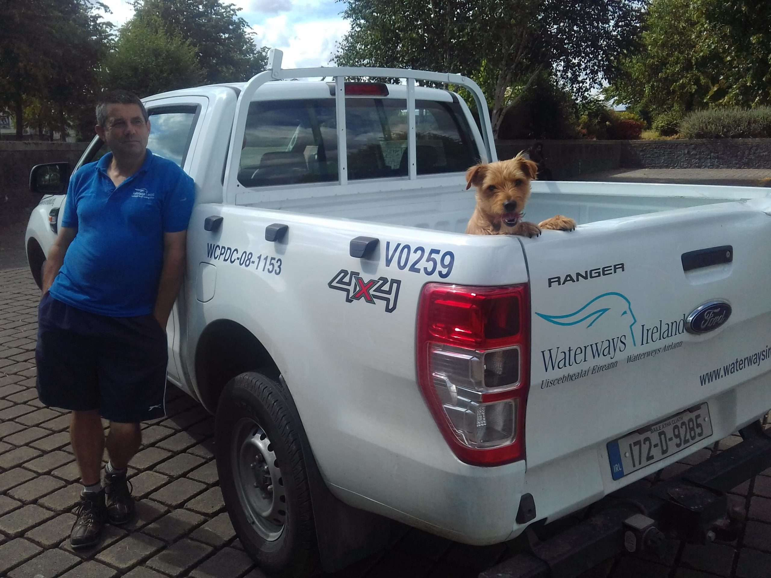 Lockkeeper William O'Neill, with a small dog in a white Waterways Ireland Jeep