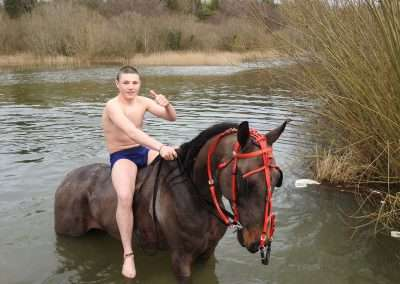 Teenager on a horse in water at Kellyville Lake, county Laois, Ireland