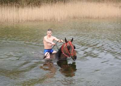 Teenage man riding a horse in a lake.