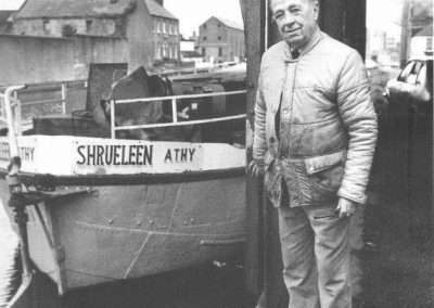 Old man beside a boat named Shruleen