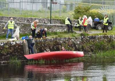Aiden Mchugh and Dan Curtis putting a canoe in the river Barrow. Litter picking staff on river bank