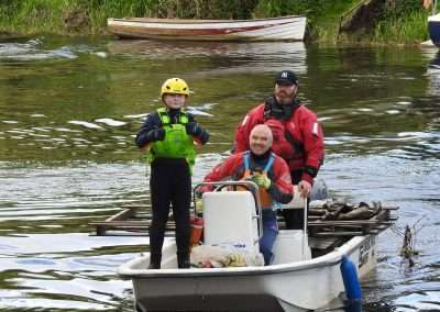 Terry Smith & Shane Smith and a young helper on a boat collecting rubbish on the river Barrow in Athy